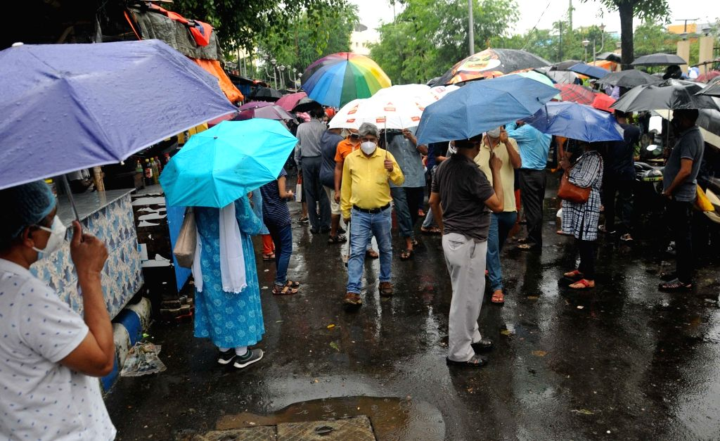 Guardians shield themselves using umbrellas during rains as they wait to receive their children outside the exam center where students are appearing for the Joint Entrance Examination (JEE) ...