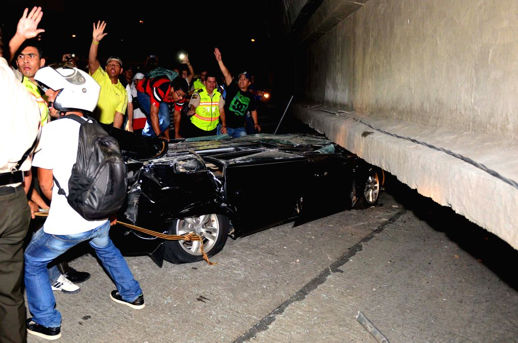 GUAYAQUIL(ECUADOR), April 17, 2016 People try to rescue a victim trapped in a vehicle crushed by a bridge after an earthquake in Guayaquil, Ecuador, on April 16, 2016. The number of ...
