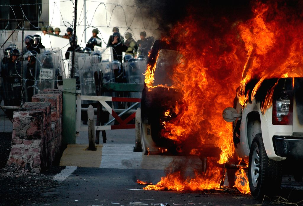 Flames emanate from a vehicle during a protest in front of the 35th Military Zone in Chilpancingo, capital of Guerrero State, Mexico, on Jan 12, 2015. According to