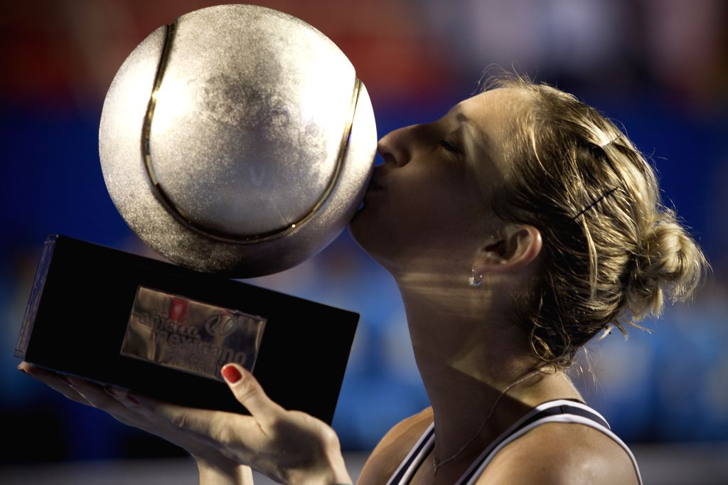 Switzerland's Timea Bacsinszky kisses the trophy after the women's singles final match against France's Caroline Garcia on the Mexican Tennis Open 2015 tournament ...
