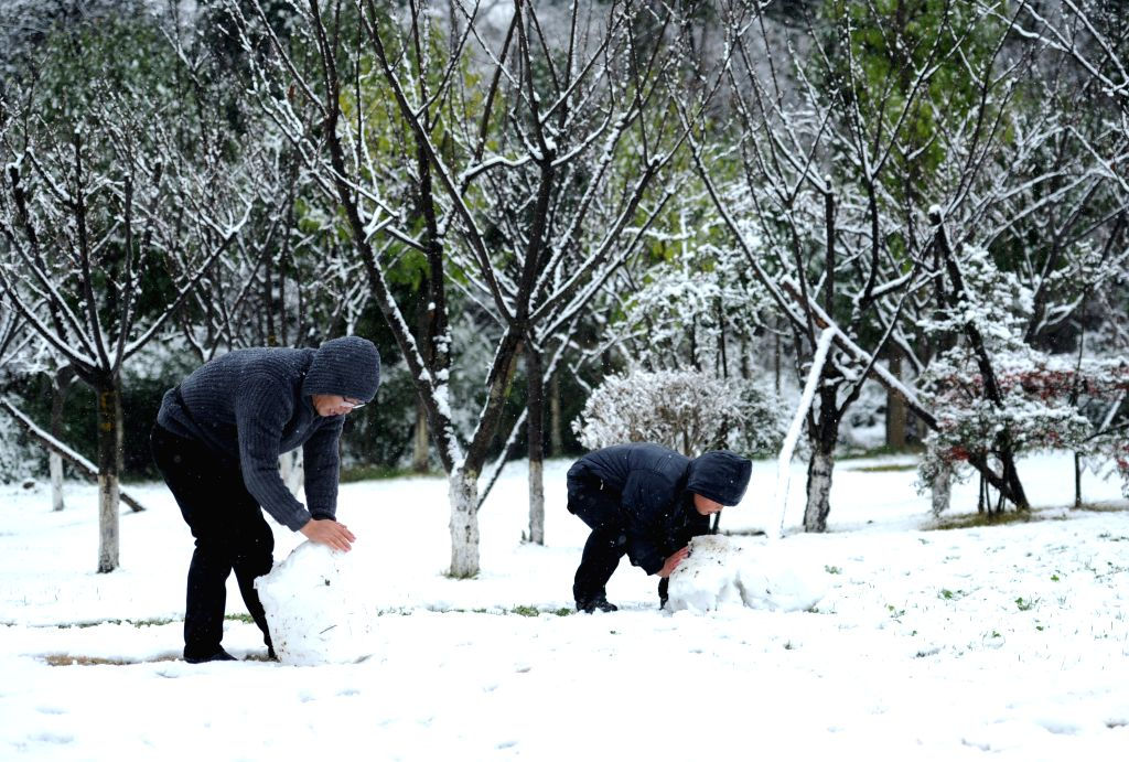 People roll snow balls in Guiyang, capital of southwest China's Guizhou Province, Jan. 9, 2015. Most parts of Guizhou saw this year's first snowfall on Friday. ...