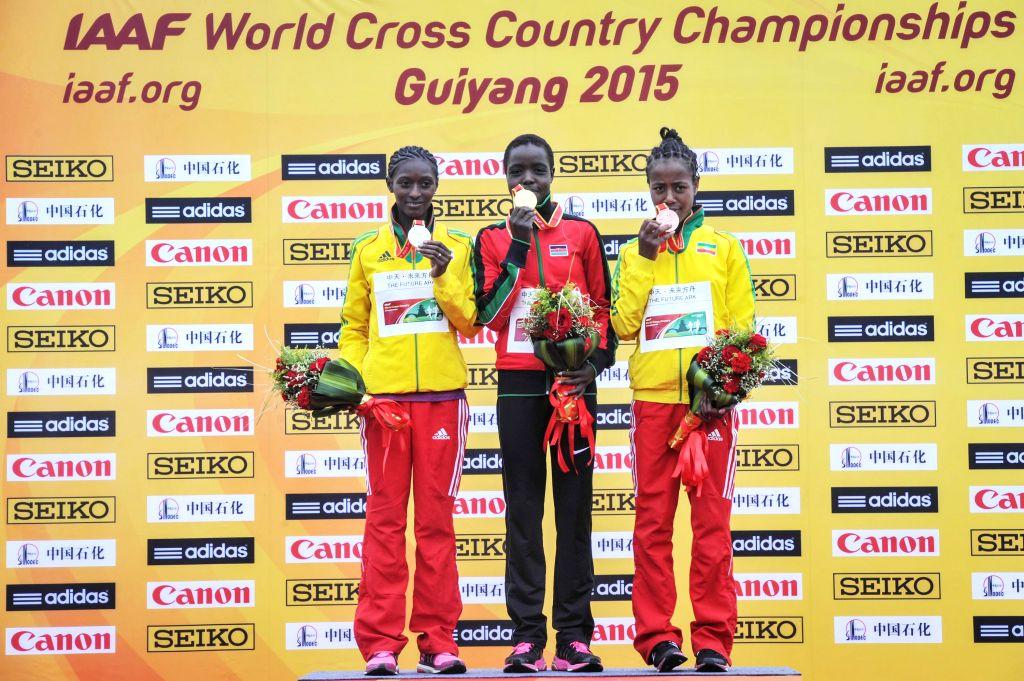Gold medalist Agnes Jebet Tirop (C) of Kenya, silver medalist Senbere Teferi (L) of Ethiopia and bronze medalist Netsanet Gudeta of Ethiopia pose on the podium ...