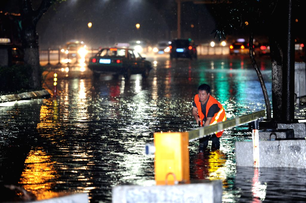 A city worker clears drain outlets of a street in the floods in Guiyang, southwest China's Guizhou Province, May 10, 2014. A heavy rain and hailstorm hit some ...