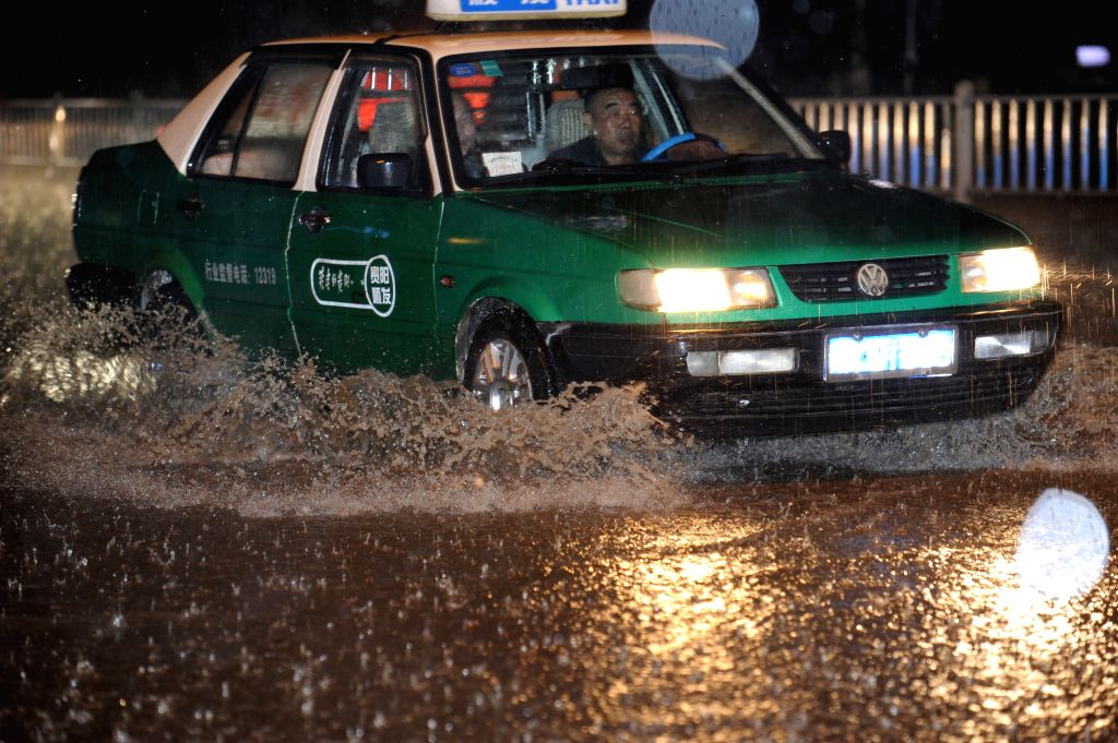 A taxi runs in the floods in Guiyang, southwest China's Guizhou Province, May 10, 2014. A heavy rain and hailstorm hit some regions of the province from late Friday.