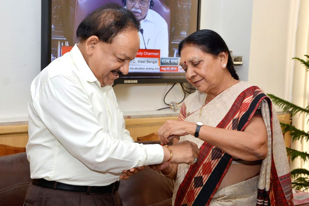 Gujarat Chief Minister Anandiben Patel ties a `rakhi` on the wrist of Union Minister for Health and Family Welfare Dr. Harsh Vardhan in New Delhi on Aug 8, 2014. - Anandiben Patel
