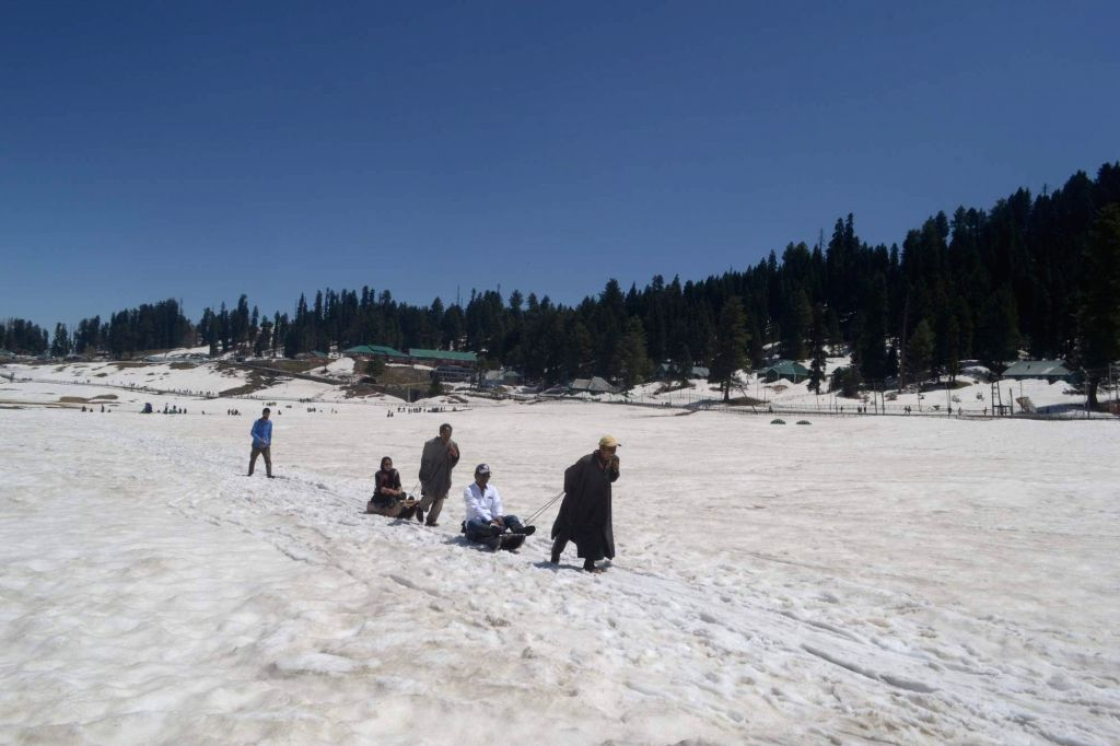 Tourists enjoy themselves on snow in Gulmarg of Jammu and Kashmir on April 25, 2015.