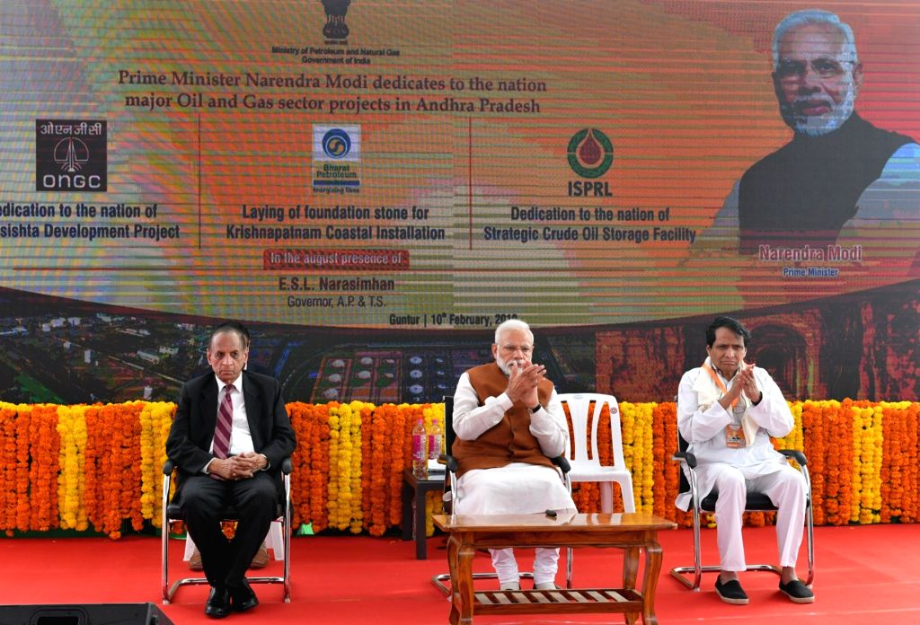 Guntur: Prime Minister Narendra Modi during a programme organied to inaugurate Oil and Gas sector Projects in Andhra Pradesh's Guntur on Feb 10, 2019. Also seen Andhra Pradesh and Telangana Governor E.S.L. Narasimhan and Union Commerce and Industry S - Narendra Modi and Suresh Prabhakar Prabhu