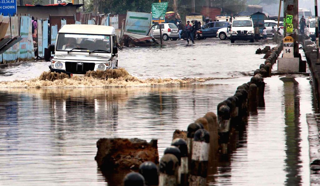 A vehicle plies on water logged National Highway - 8 in Gurgaon, on March 2, 2015.