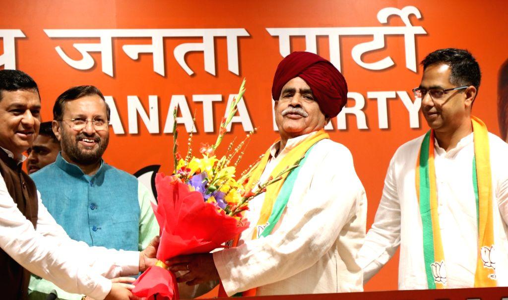 Gurjar Arakshan Sangharsh Samiti leader Kirori Singh Bainsla and his son Vijay Singh Bainsla join BJP in the presence of Union Minister Prakash Javadekar, in New Delhi, on April 10, 2019. - Prakash Javadekar, Kirori Singh Bainsla and Vijay Singh Bainsla