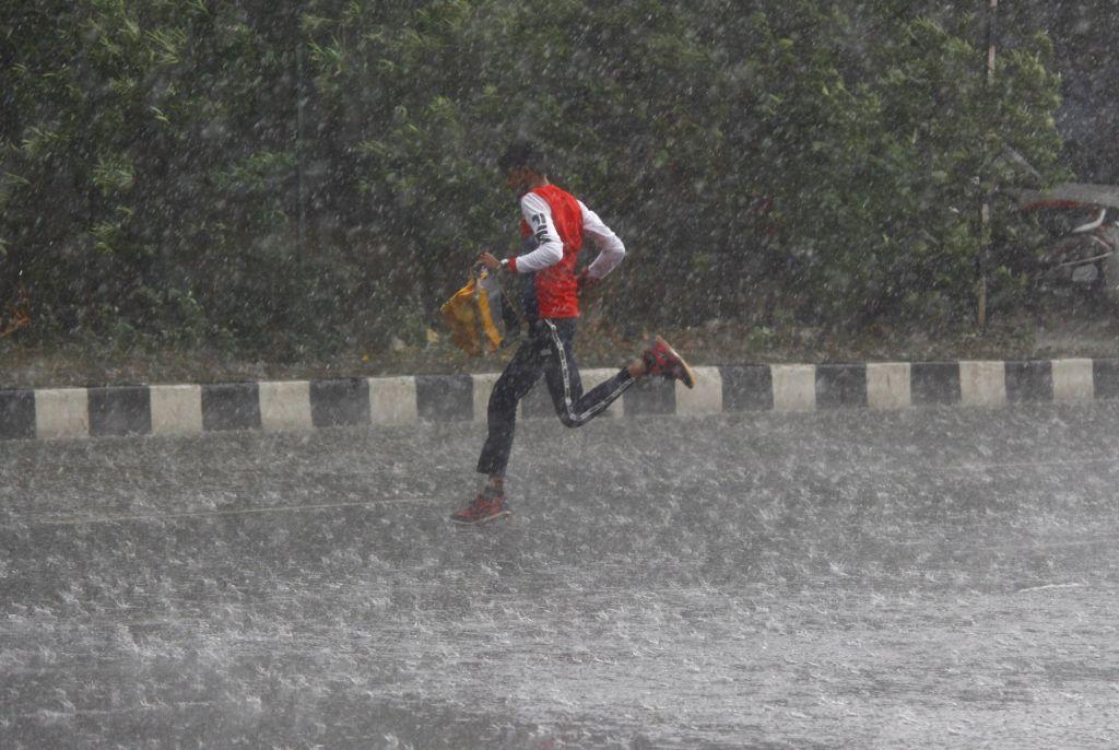 Gurugram: A boy runs for shade as heavy rains lash Gurugram, on May 17, 2019. (Photo: IANS)