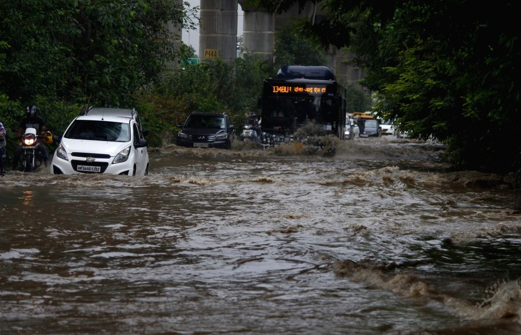 Gurugram: Vehicles wade through a water-logged road after heavy rains, in Gurugram on Aug 6, 2019. (Photo: IANS)