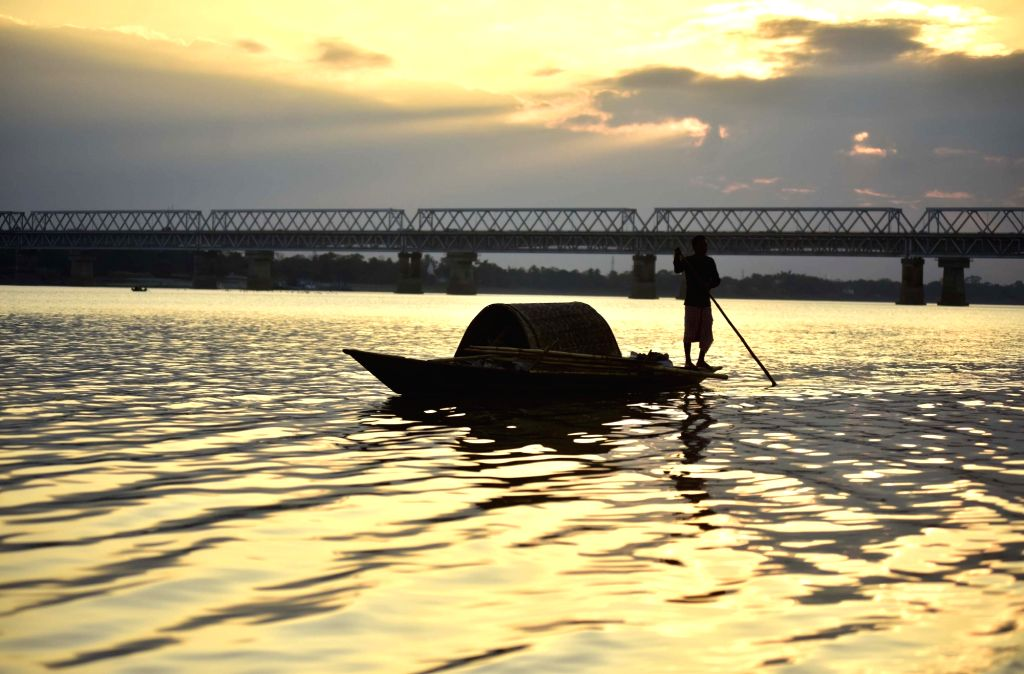 Guwahati: A fisherman rows his boat on the Brahmaputra river as he returns back home during sunset in Guwahati, on Dec 20, 2018. (Photo: IANS)