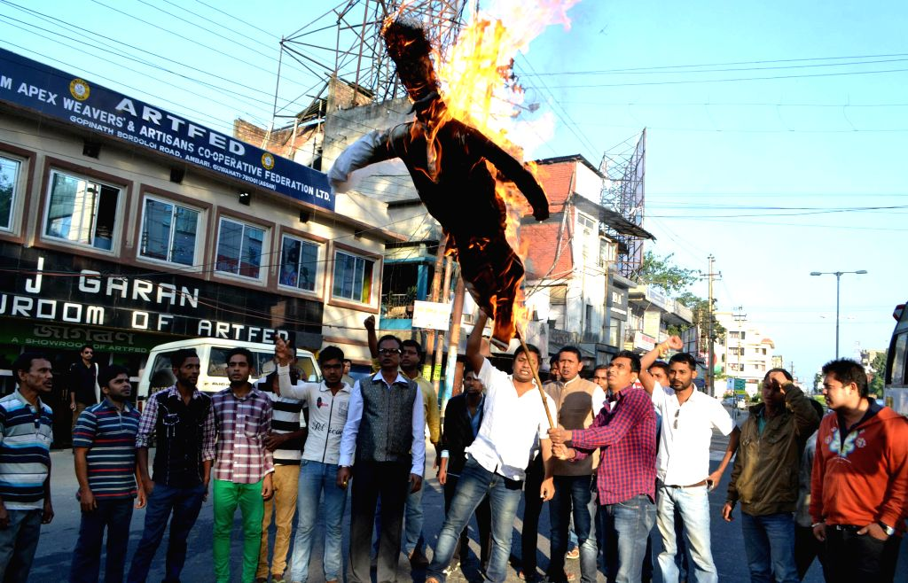 Activist of Asom Yuva Parishad burn effigies of Prime Minister Narendra Modi as they stage a demonstration against the proposed Indo-Bangladesh land swap deal in Guwahati on Dec 1, 2014. - Narendra Modi