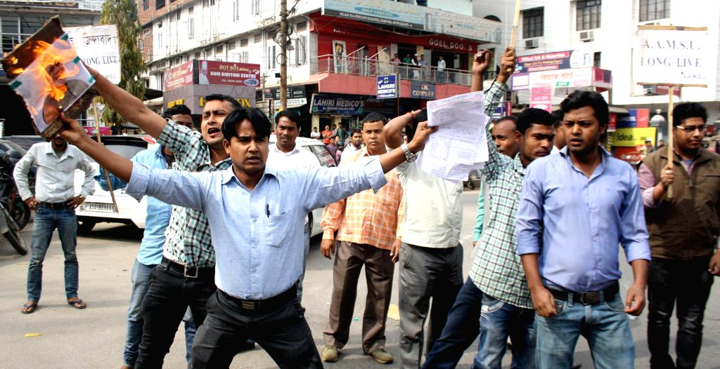 Activists of the All Assam Minorities Students union (AAMSU) burn an effigy of Prime Minister Narendra Modi in protest against BJP`s vision document for the Delhi assembly polls which ... - Narendra Modi