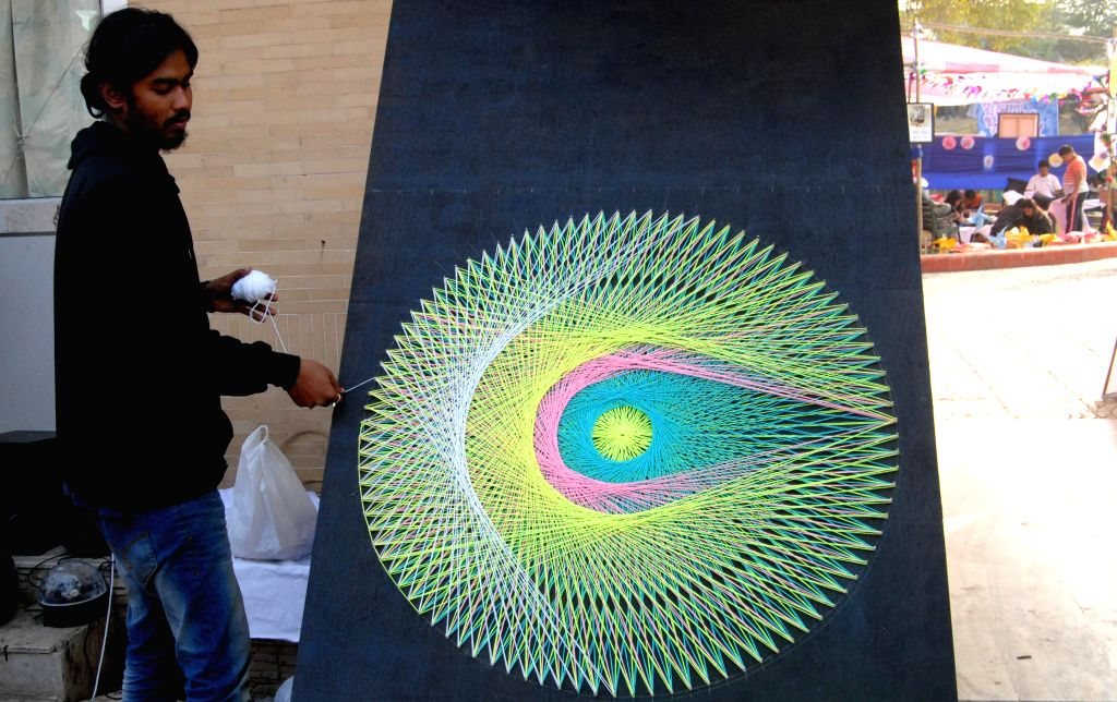 An artist makes a design with threads and nails at the Metropolis Guwahati Festival in Guwahati, on Jan 10, 2015.