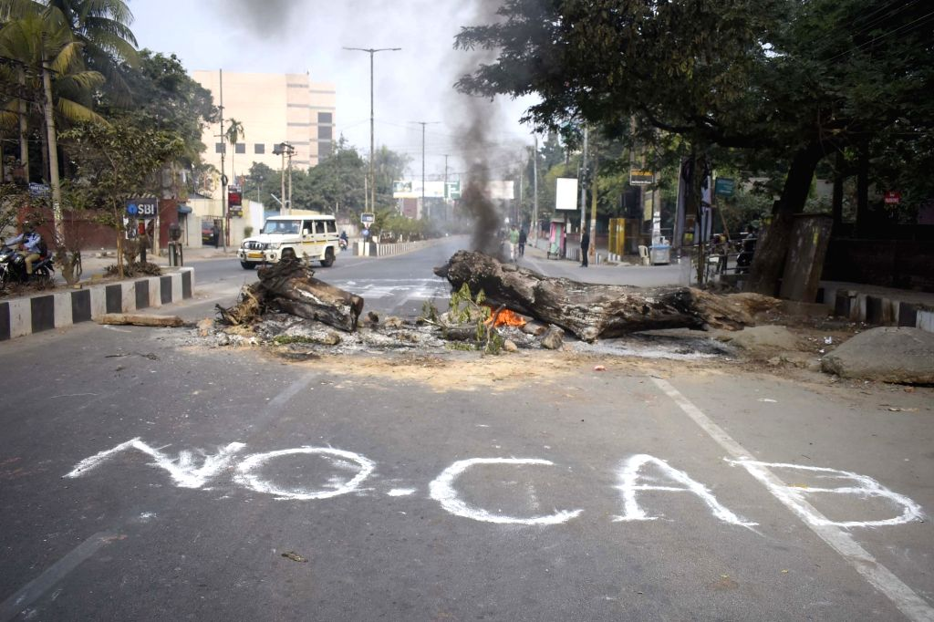 """Guwahati: Angry protesters burn tires and write """"No CAB"""" with white chalk on a street as Assam witnesses widespread violence over the Citizenship Amendment Bill (CAB) 2019; in Guwahati on Dec 12, 2019. Guwahati has become an epicentre of the anti-CAB"""