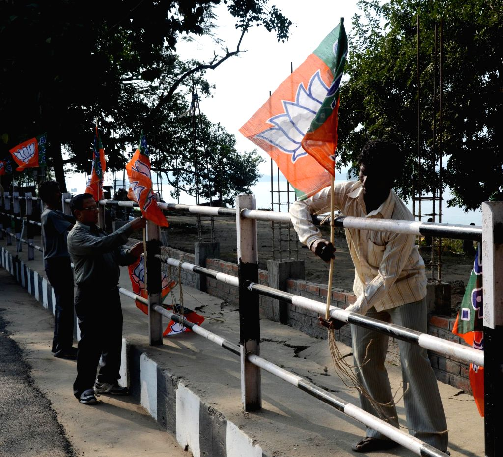BJP workers fix party flags on the railings along the roads in Guwahati ahead of Prime Minister Narendra Modi's visit, on Nov 28, 2014. - Narendra Modi