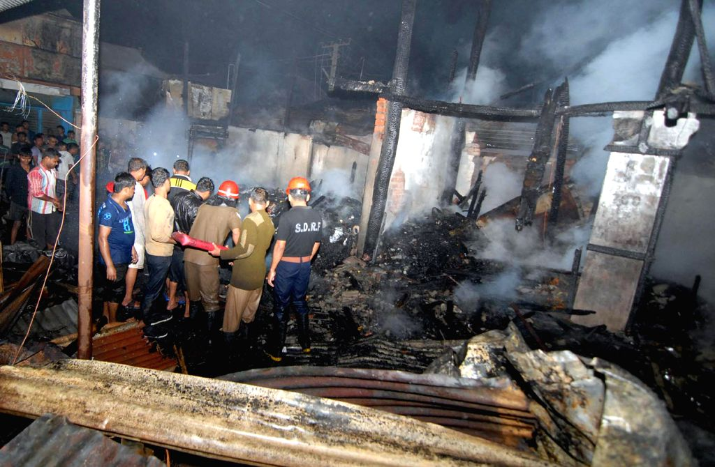 Firefighters try hard to douse a fire that broke out near Pandu Railway Bazzar in Guwahati on March 8, 2015.