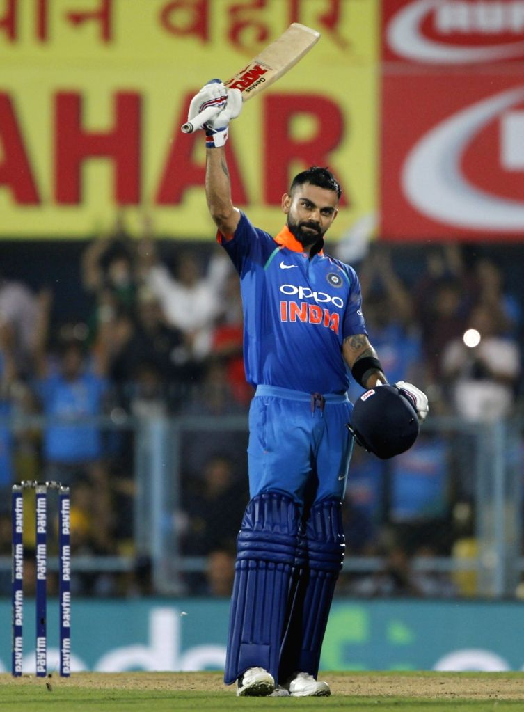 : Guwahati: Indian captain Virat Kohli celebrates his century the first ODI (One Day International) match between India and West Indies at the Barsapara Cricket Stadium in Guwahati, on Oct 21, 2018. ...