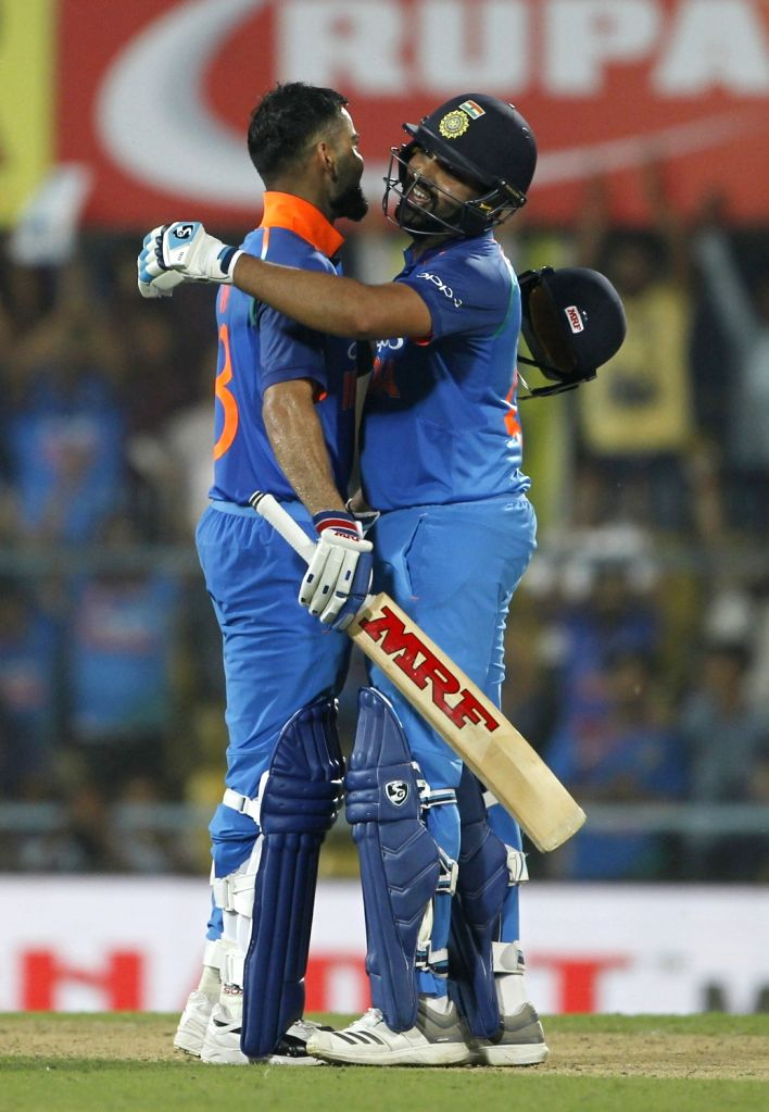 :Guwahati: Indian captain Virat Kohli celebrates his century with teammate Rohit Sharma during the first ODI (One Day International) match between India and West Indies at the Barsapara Cricket ...