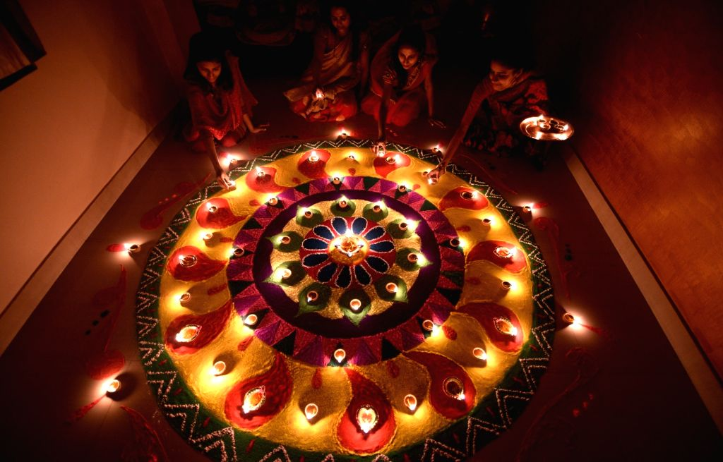 Guwahati: Women light earthen lamps on Diwali in Guwahati on Oct 19, 2017. (Photo: IANS)