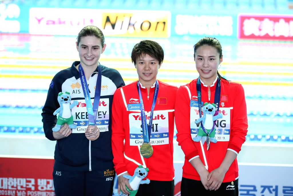 GWANGJU, July 19, 2019 - Gold medalist Shi Tingmao (C), silver medalist Wang Han (R) of China and bronze medalist Maddison Keeney of Australia pose for photos after the women's 3m springboard final ...