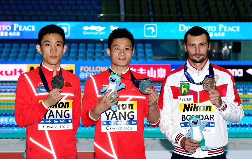 GWANGJU, July 20, 2019 - Gold medalist Yang Jian (C) of China, silver medalist Yang Hao (L) of China and bronze medalist Aleksandr Bondar pose after the medal ceremony of the men's 10m platform of ...