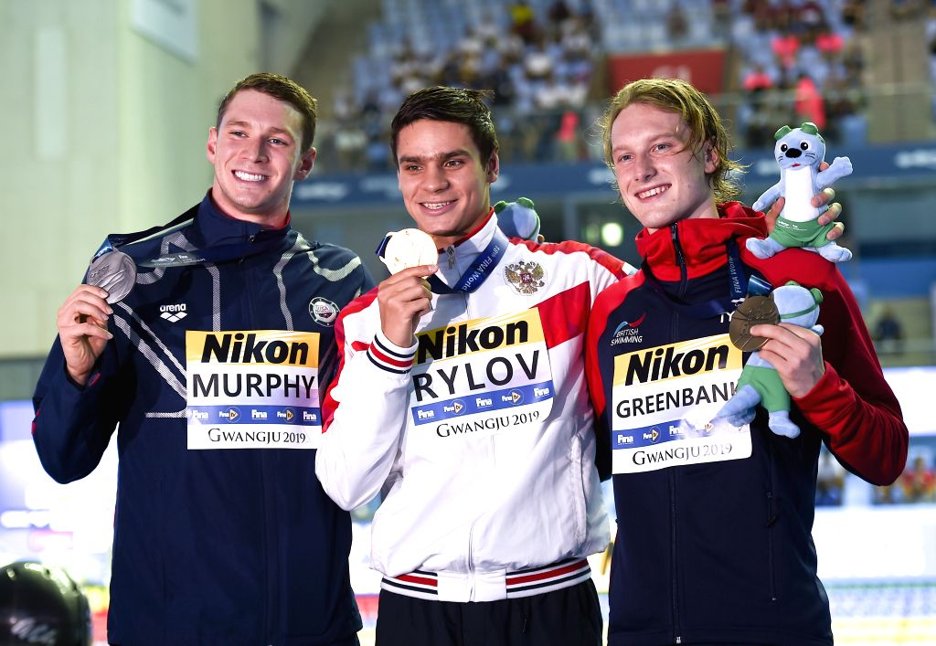 GWANGJU, July 26, 2019 - Gold medalist Evgeny Rylov (C) of Russia, silver medalist Ryan Murphy (L) of the United States and bronze medalist Luke Greenbank of Britain pose after the men's 200m ...