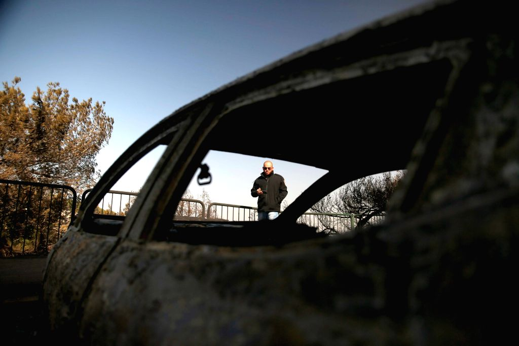 HAIFA (ISRAEL), Nov. 25, 2016 A man looks at fire damaged cars in Haifa, Israel, on Nov. 25, 2016. Fires on Thursday forced a widespread evacuation in Haifa, as foreign countries sent in ...