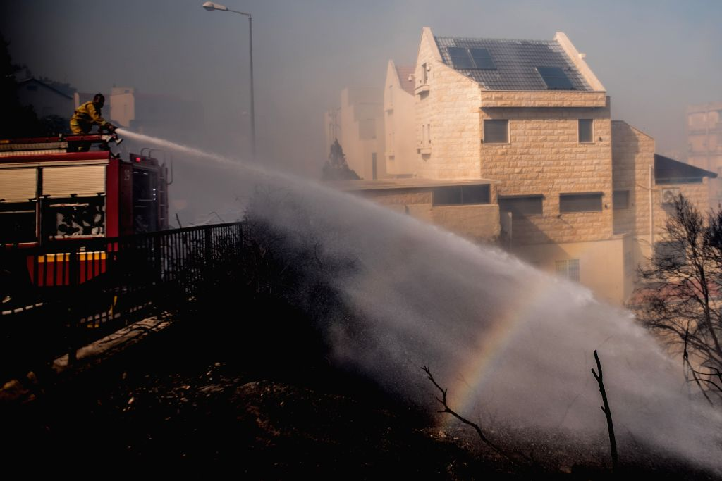 HAIFA, Nov. 25, 2016 - A firefighter tries to extinguish a fire in Haifa, Israel, Nov. 24, 2016. Fires on Thursday forced a widespread evacuation in Haifa. Tens of thousands of residents were forced ...