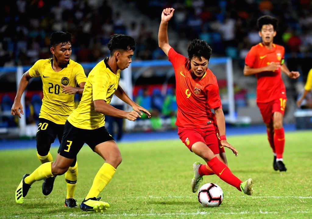 HAIKOU, July 20, 2019 - Zeng Yaozhang (R) of China vies with Adam Daniel (2nd L) of Malaysia during a China International Youth Football Tournament Haikou 2019 match between Malaysia U-15 and China ...