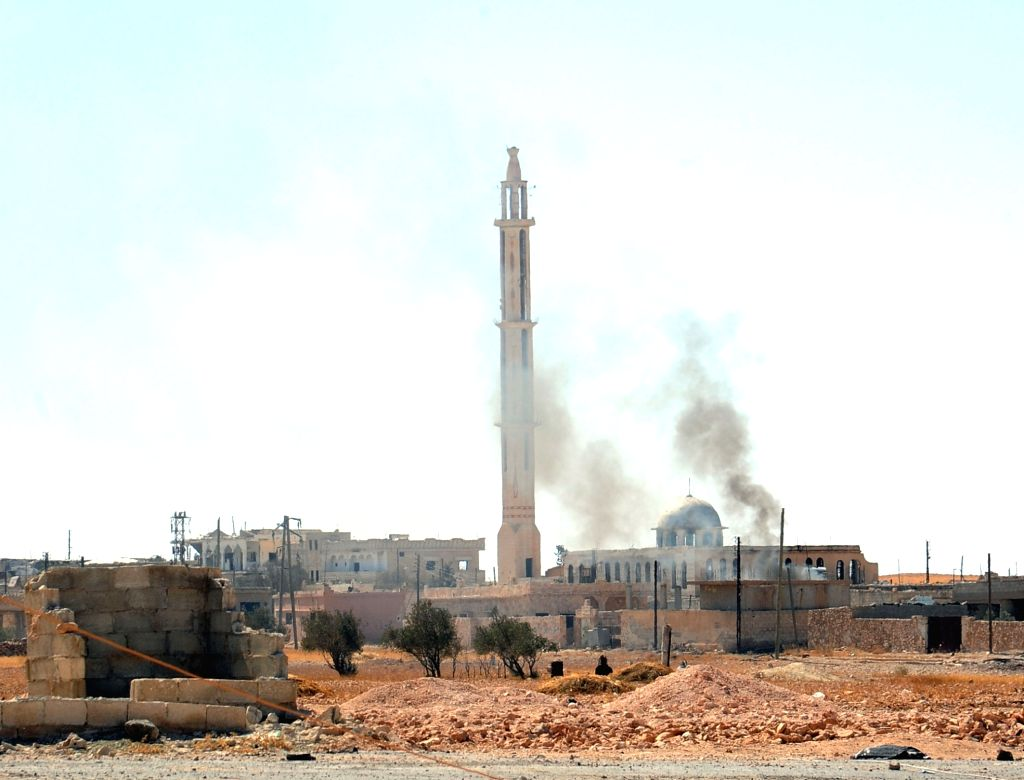 HAMA (SYRIA), Oct. 3, 2017 Smoke rises in front of a damaged mosque in a recently captured town in Hama, Syria, on Oct. 3, 2017. The Syrian army succeeded on Tuesday to slice through an ...