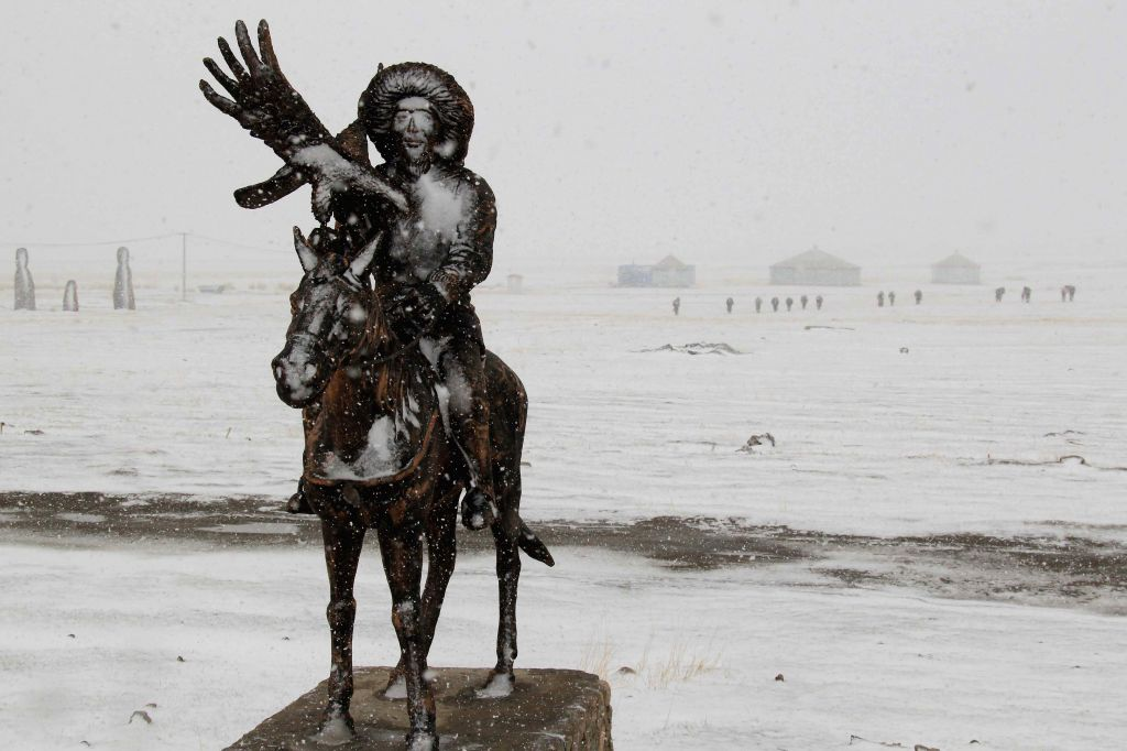 A snow-covered sculpture of herdsman is seen on the snow-covered Barkol Grassland in Hami, northwest China's Xinjiang Uygur Autonomous Region, April 15, 2014. The ...