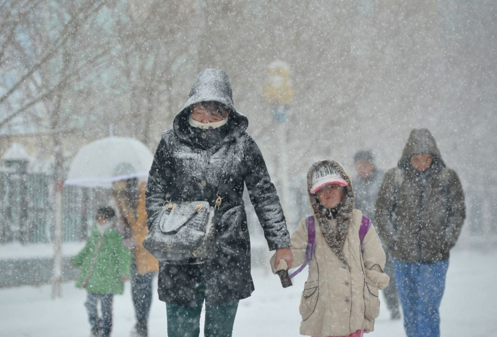 A woman and a young girl walk in snow at Kazak Autonomous County of Barkol in Hami, northwest China's Xinjiang Uygur Autonomous Region, April 17, 2014. A snowfall hit