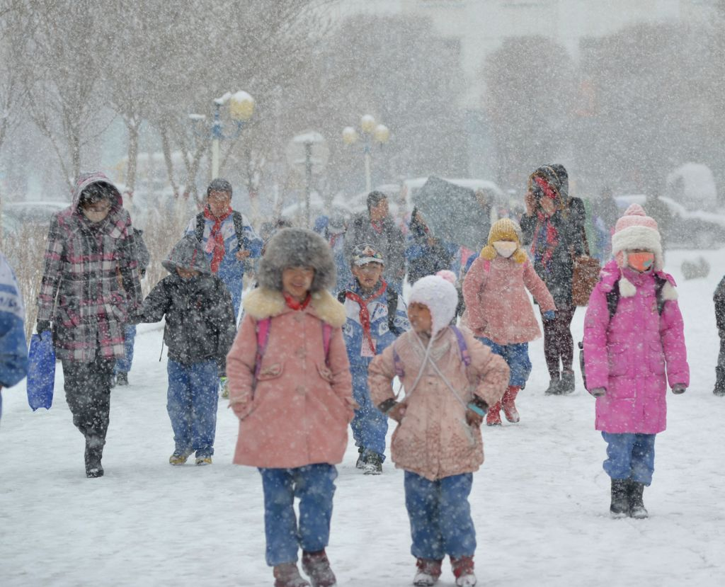 Pupils walk in snow at Kazak Autonomous County of Barkol in Hami, northwest China's Xinjiang Uygur Autonomous Region, April 17, 2014. A snowfall hit the county on ...