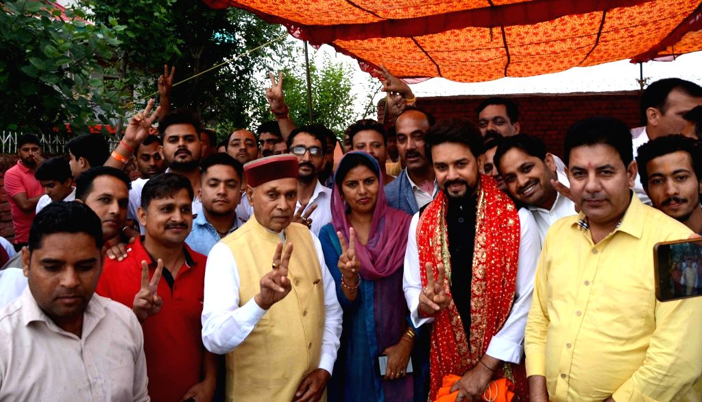 Hamirpur: BJP Lok Sabha candidate, Anurag Thakur accompanied by his father-former Himachal Pradesh Chief Minister Prem Kumar Dhumal, celebrates after he emerged victorious from the Hamirpur Lok Sabha constituency in the recently concluded 2019 Lok Sa - Prem Kumar Dhumal