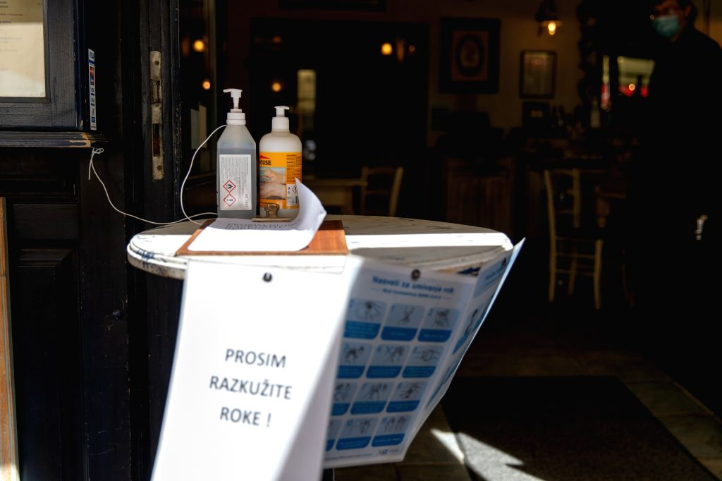 Hand sanitizers are seen at the door of a restaurant for customers to use in Ljubljana, Slovenia, on May 8, 2020. Slovenia's COVID-19 death toll has risen to 100 ...