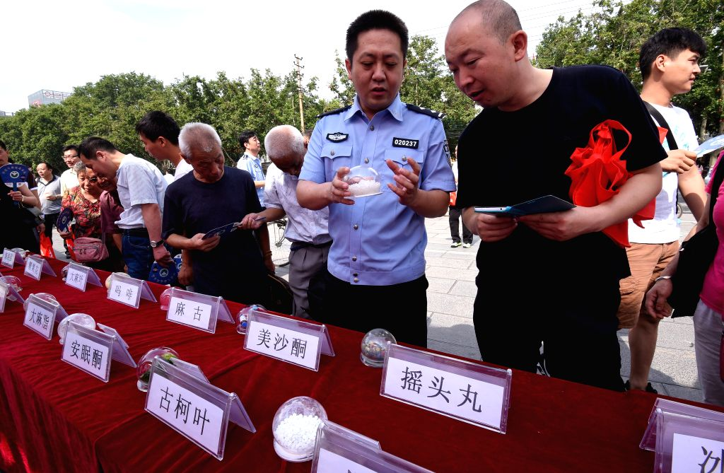 HANDAN, June 26, 2016 - A policeman introduces harm of drug to citizens in Handan, north China's Hebei Province, June 26, 2016. A variety of educational activities were held across the country on ...