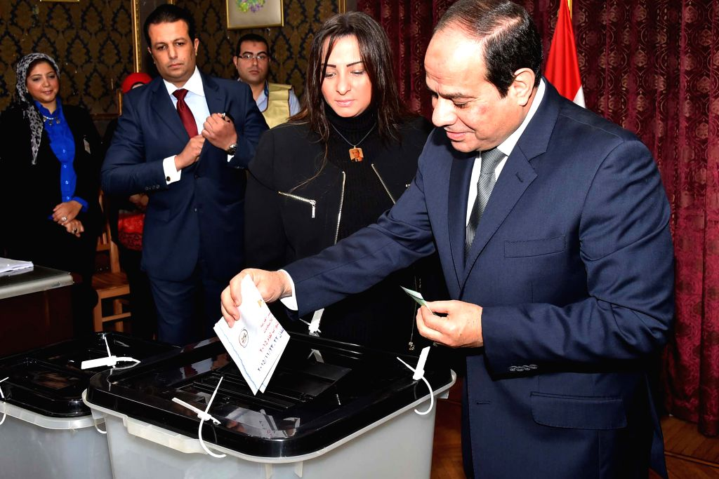 Handout photo from Egypt's state-run MENA news agency shows that Egypt's President Abdel Fattah al-Sisi (1st R) casting his ballot at a polling station in Cairo, ...