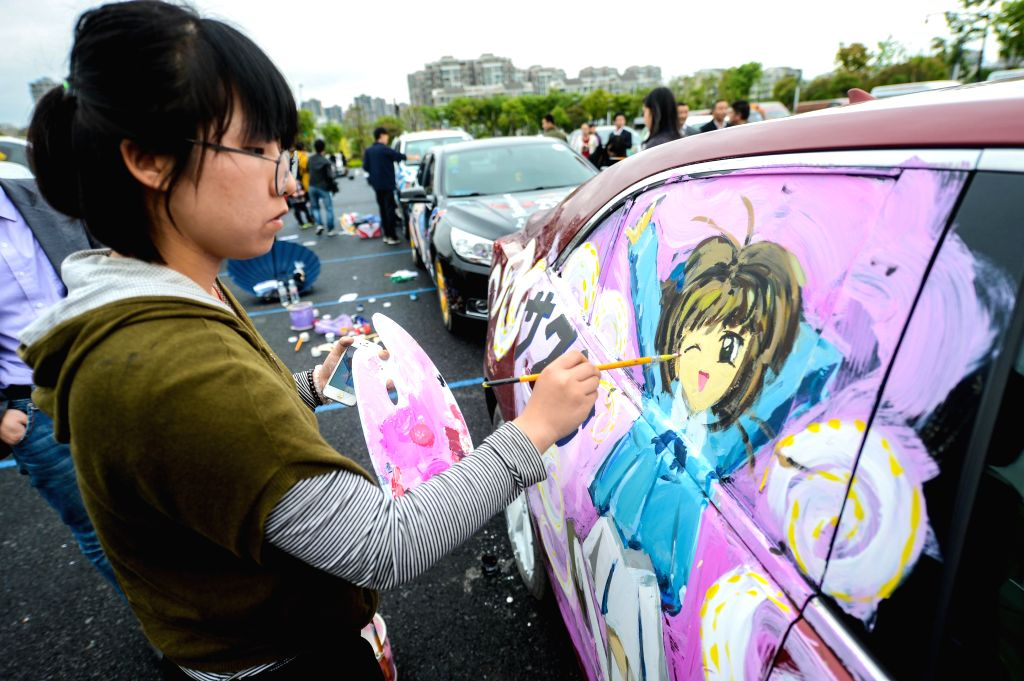 A woman paints cartoon elements on her car during an automobile parade held in Hangzhou, capital of east China's Zhejiang Province, April 27, 2014. Some 100 cars .