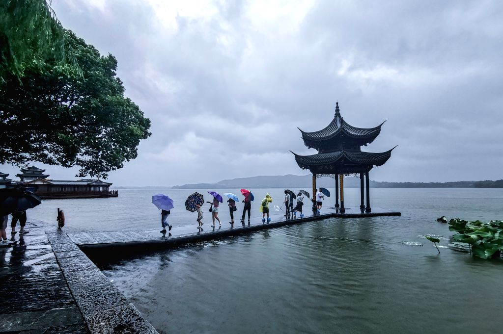 HANGZHOU, Aug. 10, 2019 - Mobile photo shows people visiting West Lake scenic area in the rain in Hangzhou, east China's Zhejiang Province, Aug. 10, 2019. Affected by Typhoon Lekima Hangzhou has ...