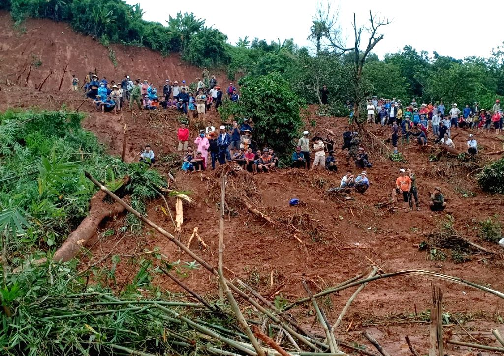 HANOI, Aug. 9, 2019 - People stand at a landslide site in Dak Nong province, Vietnam, on Aug. 8, 2019. As of Friday afternoon, floods and landslides in Vietnam's central highlands region had killed ...