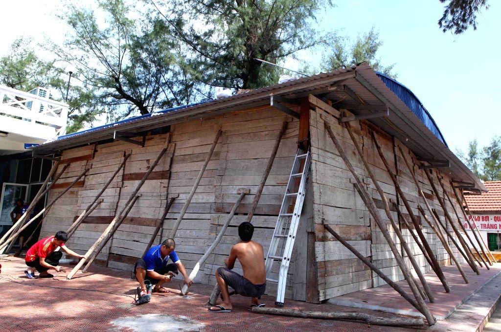 Residents reinforce house to prepare bracing for Typhoon Rammasun in Hai Phong city, north Vietnam, July 18, 2014. Typhoon Rammasun is forecast to make landfall in ...