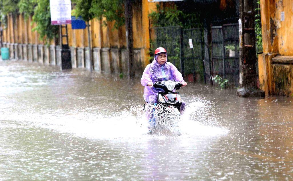 HANOI, July 21, 2018 - A motorist wades through flood after heavy rain brought by Typhoon Son Tinh in Hanoi, capital of Vietnam, July 21, 2018.