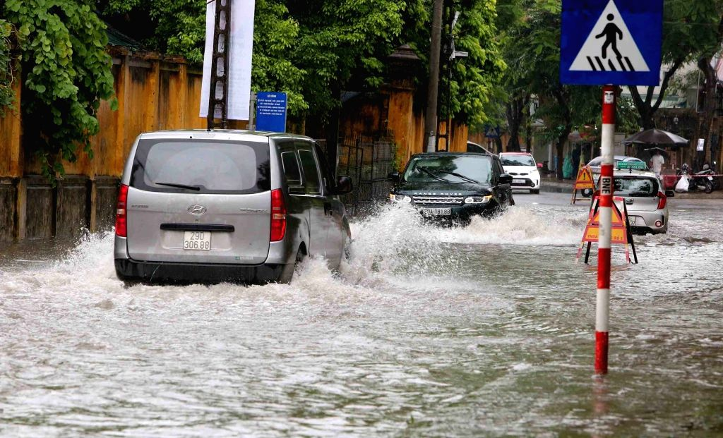 HANOI, July 21, 2018 - Cars move through flood after heavy rain brought by Typhoon Son Tinh in Hanoi, capital of Vietnam, July 21, 2018.
