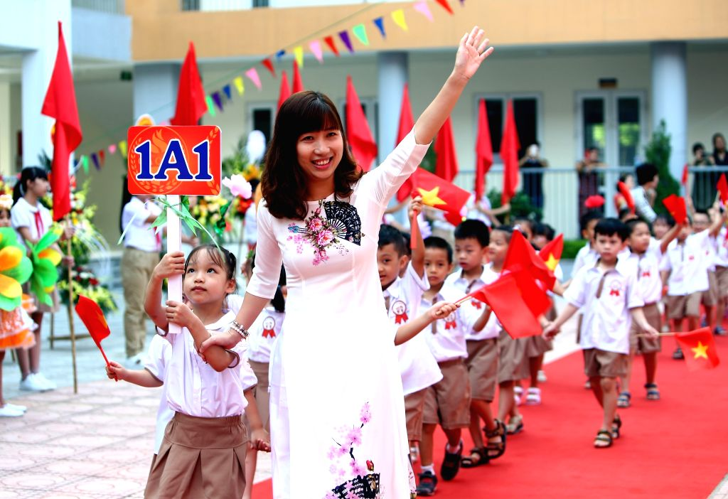 HANOI, Sept. 5, 2019 - A teacher and her students attend a ceremony opening the new school year in Hanoi, Vietnam, on Sept. 5, 2019. More than 24 million students across Vietnam began the 2019-2020 ...