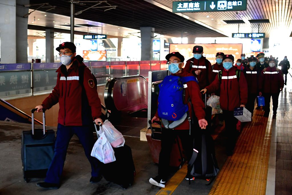 Hao Tiedan (2nd L) and his team members walk to board a train at Taiyuan South Railway Station in Taiyuan, north China's Shanxi Province, Feb. 5, 2020. Hao Tiedan is ...