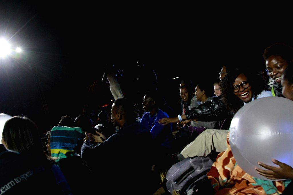 People camp out to watch the performance on the opening ceremony of the six-day Harare International Festival of The Arts (HIFA), Harare, capital of Zimbabwe, on ...