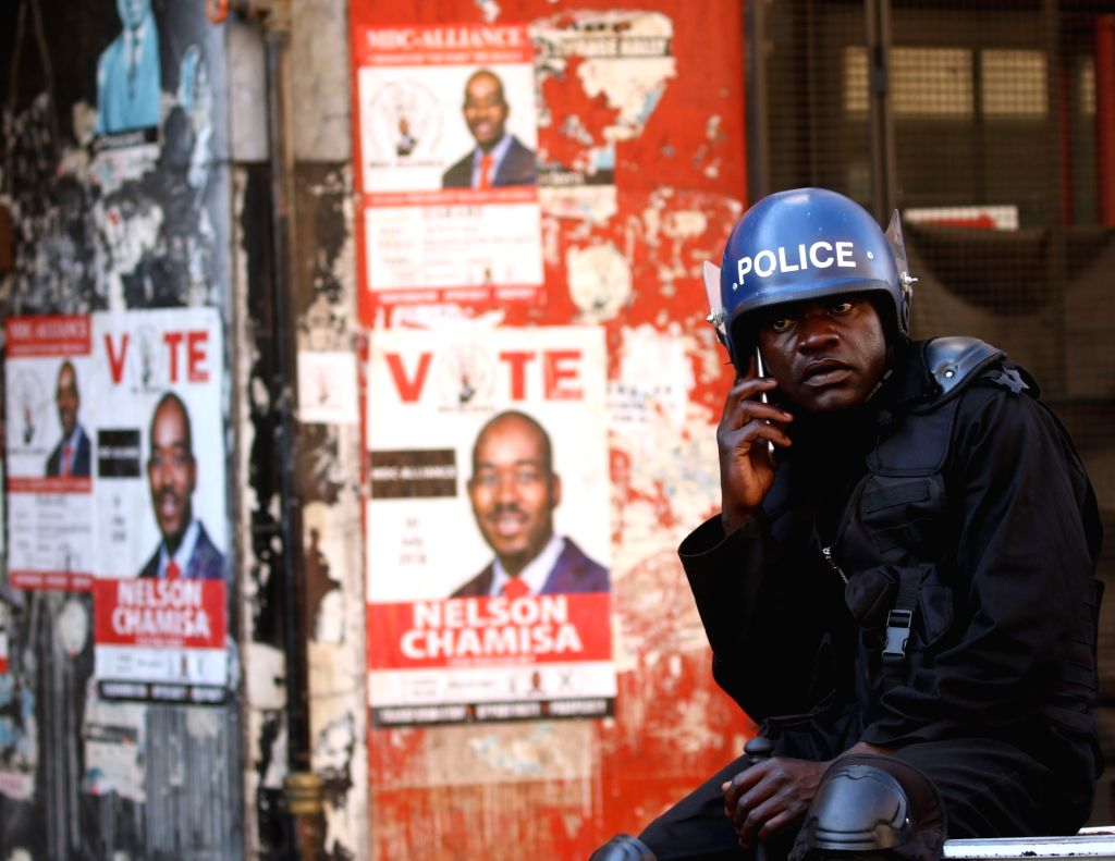 HARARE, Aug. 2, 2018 - An anti-riot policeman talks on the cellphone near the headquarters of the opposition MDC (Movement For Democratic Change) Alliance  in Harare, Zimbabwe, Aug. 2, 2018. Police ...