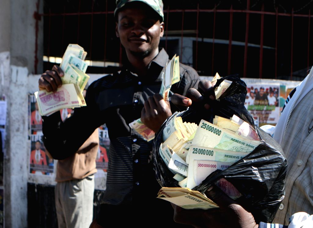 HARARE, Aug. 4, 2016 - A man displays old Zimbabwean dollar notes while taking part in a protest against the introduction of new bond notes in Harare, Zimbabwe, Aug. 3, 2016. Zimbabwean police on ...